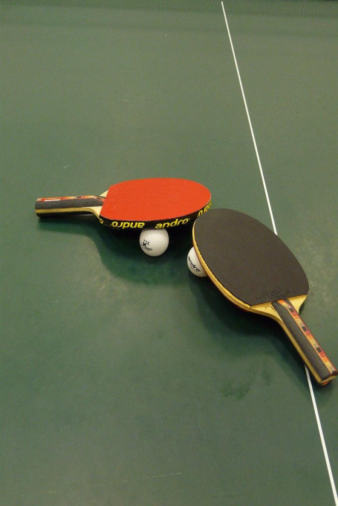 Tischtennisschläger und -bälle auf grüner Tischtennisplatte